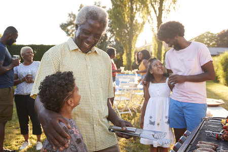 Grandad and dad talking with kids at a family barbecue Stock Photo
