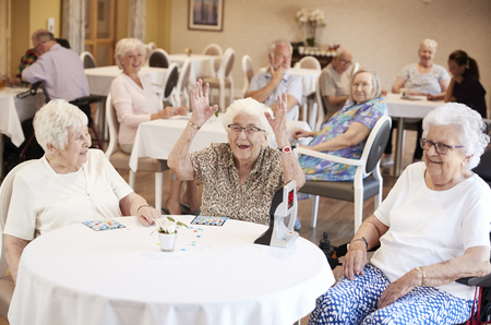 Senior Woman Winning Game Of Bingo In Retirement Home