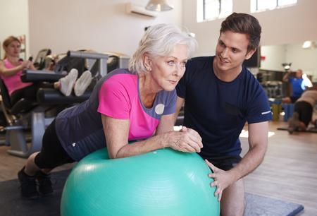 Senior Woman Exercising On Swiss Ball Being Encouraged By Personal Trainer In Gym Imagens