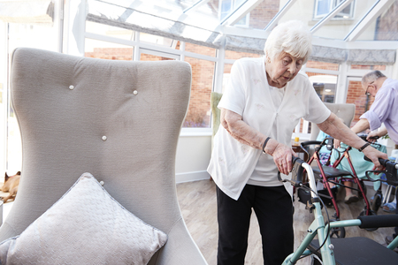 Senior Woman Using Mobility Aid In Lounge Of Retirement Home
