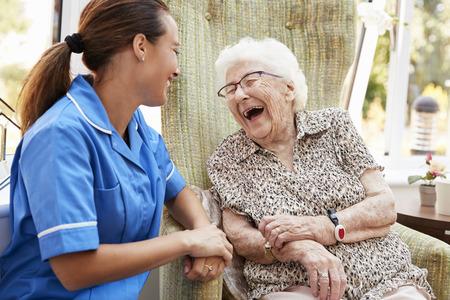 Ältere Frau, die im Stuhl sitzt und mit Krankenschwester im Altersheim lacht