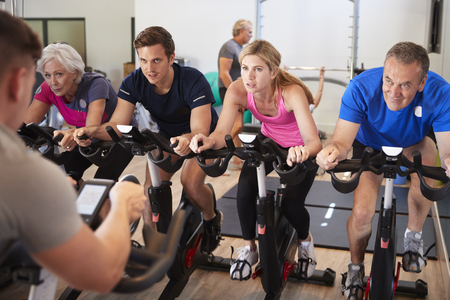 Male Trainer Taking Spin Class In Gym