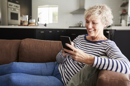 Senior white woman sitting on couch at home using smartphone Stock Photo