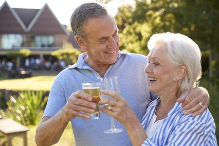 Senior Couple Enjoying Outdoor Summer Drink At Pub