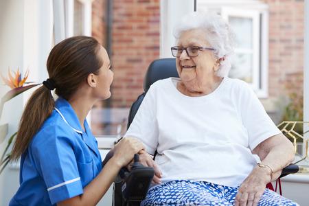 Ältere Frau, die im motorisierten Rollstuhl sitzt und mit Krankenschwester im Altersheim spricht Standard-Bild