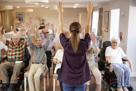 Cuidador grupo líder de personas mayores en clase de gimnasia en casa de retiro Foto de archivo