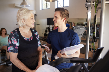 Senior Woman Exercising On Cycling Machine Being Encouraged By Male Personal Trainer In Gym