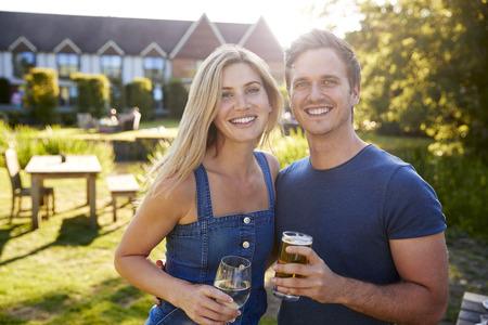 Porträt des Paares, das Sommergetränk im Freien im Pub genießt