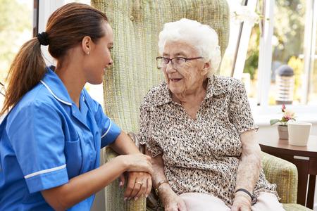 Ältere Frau, die im Stuhl sitzt und mit Krankenschwester im Altersheim spricht