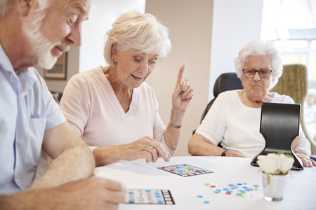 Group Of Seniors Playing Game Of Bingo In Retirement Home Archivio Fotografico