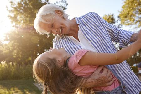 Großmutter spielt Spiel und tanzt mit Enkelin im Sommerpark