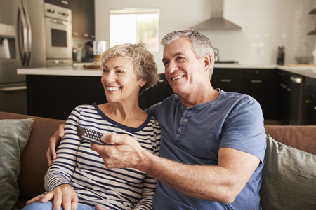 Senior couple sitting on couch watching television, close up Banque d'images - 109544028