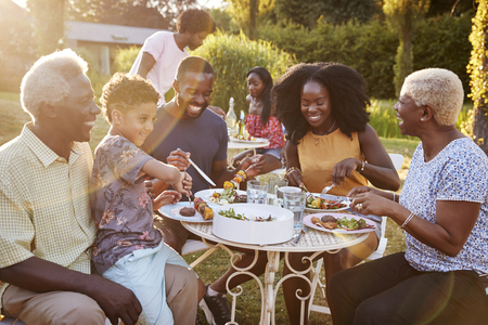 Black multi generation family eating at a table in garden Banco de Imagens