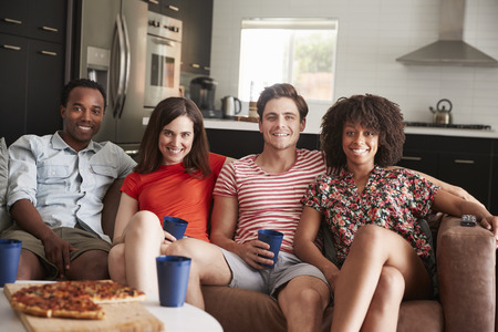 Four young adult friends relaxing on couch together at home Stock Photo