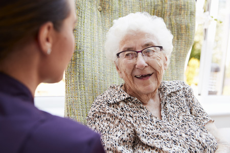 Female Resident Sitting In Chair And Talking With Carer In Retirement Home