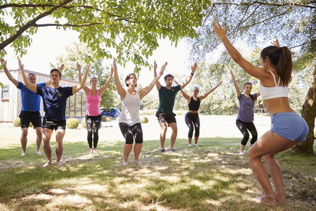 Female Instructor Leading Outdoor Yoga Class