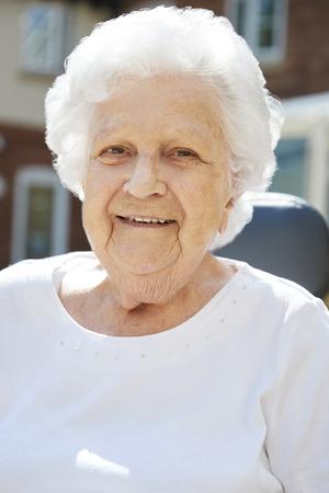 Portrait Of Senior Woman Sitting Outside Retirement Home