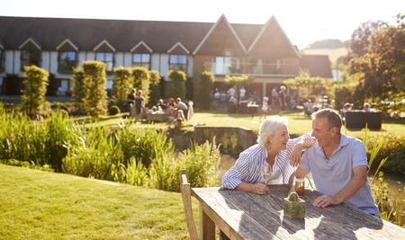 Senior Couple Sitting At Table Enjoying Outdoor Summer Drink At Pub
