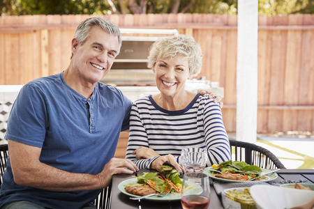 Senior white couple sit at lunch in garden looking to camera Stock Photo