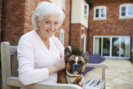 Portrait Of Senior Woman Sitting On Bench With Pet French Bulldog In Assisted Living Facility Stockfoto