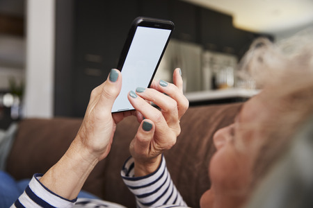 Senior woman lying on couch using smartphone, close up
