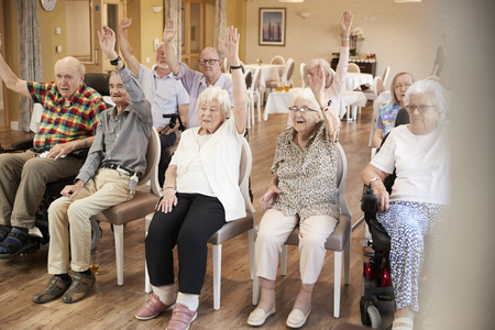 Group Of Seniors Enjoying Fitness Class In Retirement Home