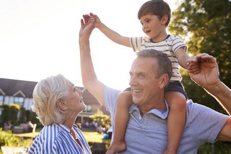 Grandparents Giving Grandson Ride On Shoulders In Summer Park Against Flaring Sun
