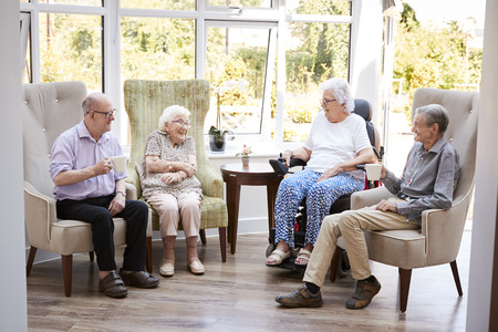 Male And Female Residents Sitting In Chairs And Talking In Lounge Of Retirement Home Stock Photo