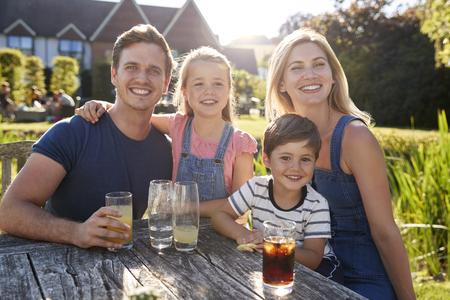 Portrait Of Family Enjoying Outdoor Summer Drink At Pub