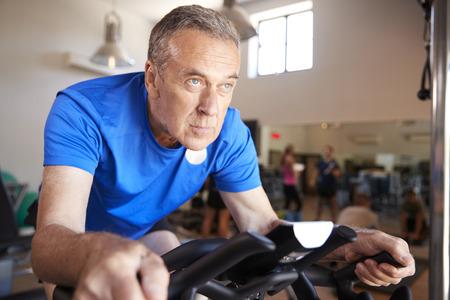 Senior Man Exercising On Cycling Machine In Gym Stock Photo