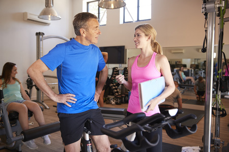 Senior Man Exercising On Cycling Machine Being Encouraged By Female Personal Trainer In Gym Stock Photo