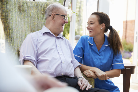 Senior Man Sitting In Chair And Talking With Nurse In Retirement Home