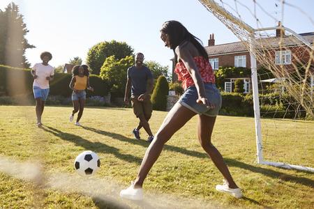 Black woman saving goal during a game of football in garden Stock Photo