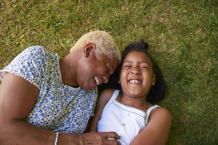 Black girl and grandmother lying on grass, overhead close up Stock Photo