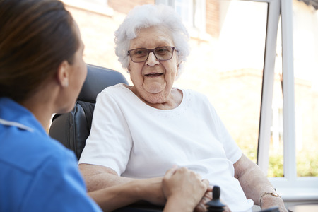 Senior Woman Sitting In Motorized Wheelchair Talking With Nurse In Retirement Home