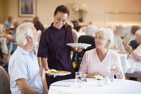 老人ホームのダイニングルームで介護者が食事を提供しているシニアカップル