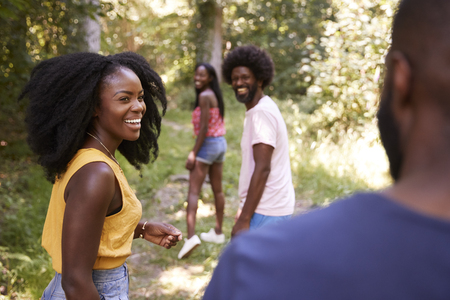 Four black adult friends walking in a forest, close up