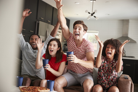 Four young adult friends watching sports on TV celebrating Banque d'images - 109544365
