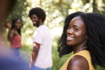 Young black woman in a forest with friends turning to camera Archivio Fotografico
