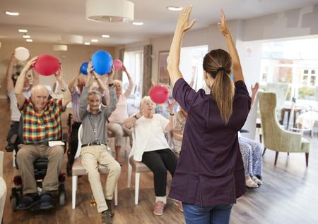 Cuidador grupo líder de personas mayores en clase de gimnasia en casa de retiro