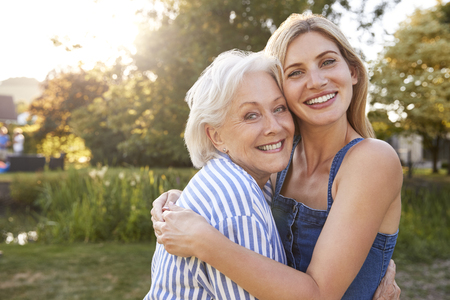 Portrait Of Smiling Mother Hugging Adult Daughter Outdoors In Summer Park Stock Photo