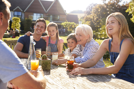 Multi Generation Family Sitting At Table Enjoying Outdoor Summer Drink At Pub Stock Photo