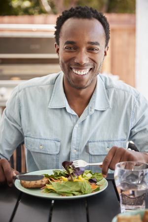 Young black man eating lunch at a table outside, vertical Stock Photo