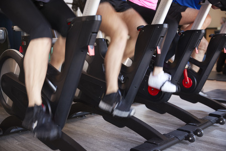 Close Up Of Feet On Exercise Bikes In Gym Spinning Class Фото со стока