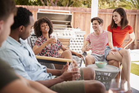 Young adult friends relaxing on the porch outside a house
