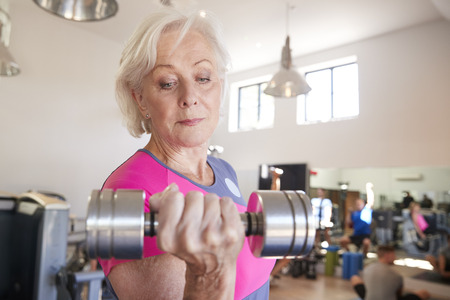 Senior Woman Exercising With Weights In Gym