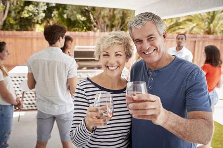 Senior couple at a backyard party raising glasses to camera Stock Photo