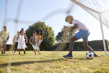 Kids scoring goal against dad during family football game