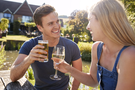 Couple Sitting At Table Enjoying Outdoor Summer Drink At Pub