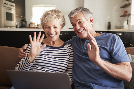 Senior couple video calling on a laptop waving at screen